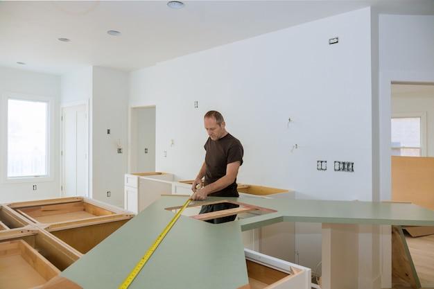Uomo che utilizza la misura di nastro per la misurazione della dimensione del controsoffitto di legno nella cucina moderna per il miglioramento domestico.