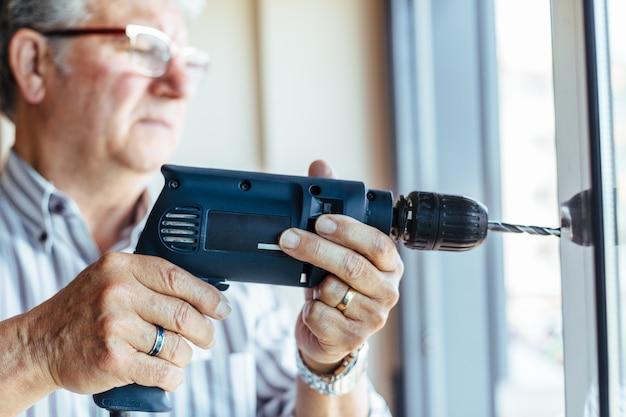 Uomo che utilizza la perforatrice