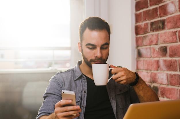 Uomo che utilizza mobile e laptop a casa la mattina, bevendo caffè
