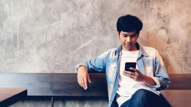 Uomo che utilizza smartphone, durante il tempo libero. il concetto di usare il telefono è essenziale nella vita di tutti i giorni.