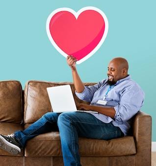 Uomo che utilizza un computer portatile e che tiene un'emoticon del cuore