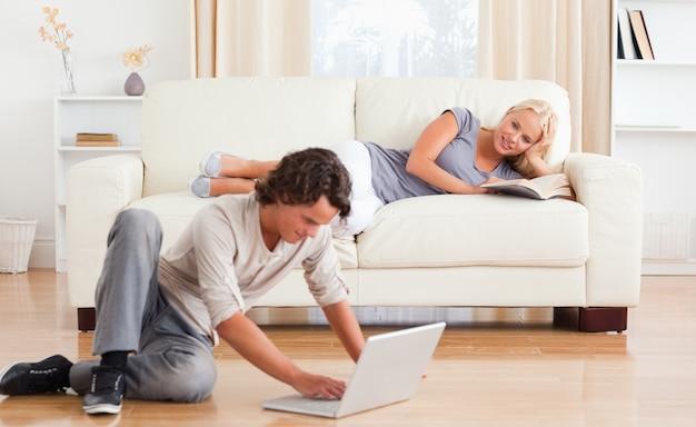 Uomo che utilizza un computer portatile mentre la sua ragazza è in possesso di un libro