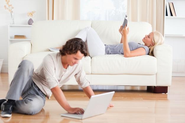 Uomo che utilizza un laptop mentre sua moglie sta leggendo un libro