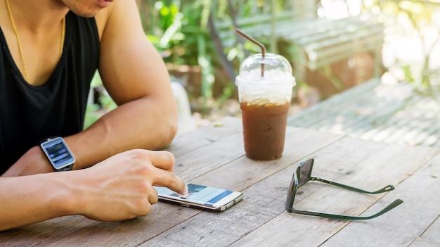 Uomo che utilizza uno smartphone in un coffee shop.