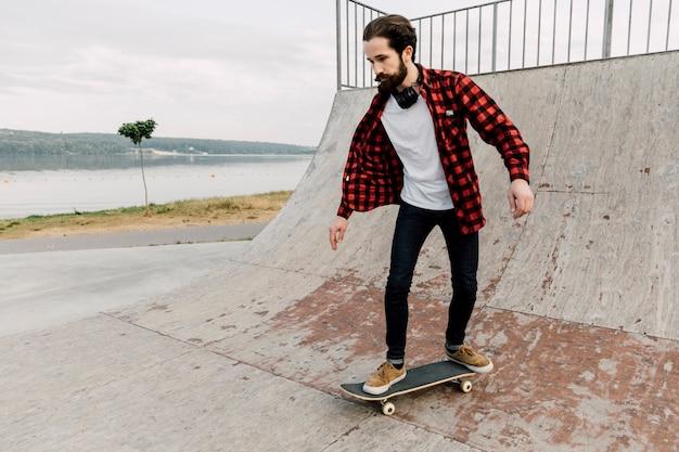 Uomo che va su una rampa a skate park