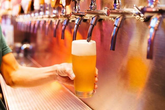 Uomo che versa birra artigianale da rubinetti della birra in vetro ghiacciato con schiuma.
