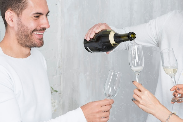 Uomo che versa champagne in bicchieri in festa