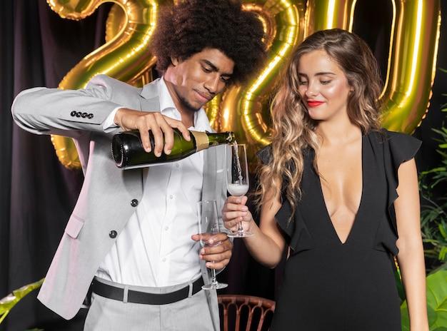 Uomo che versa champagne in vetro tenuto da donna