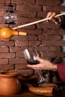 Uomo che versa il vino rosso dalla bottiglia di legno nel bicchiere