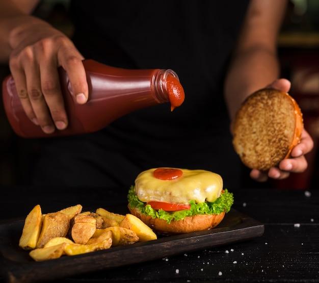 Uomo che versa ketchup su gustoso hamburger di manzo