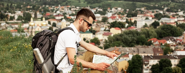 Uomo che viaggia da solo leggendo la mappa