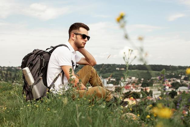 Uomo che viaggia da solo riposo sul campo verde