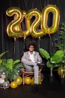 Uomo circondato da palloncini d'oro di felice anno nuovo 2020