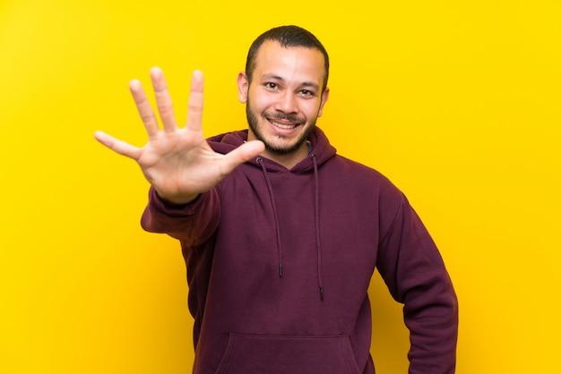 Uomo colombiano con felpa oltre muro giallo contando cinque con le dita