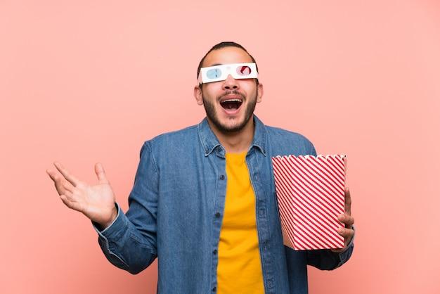 Uomo colombiano con popcorn con sorpresa ed espressione facciale scioccata