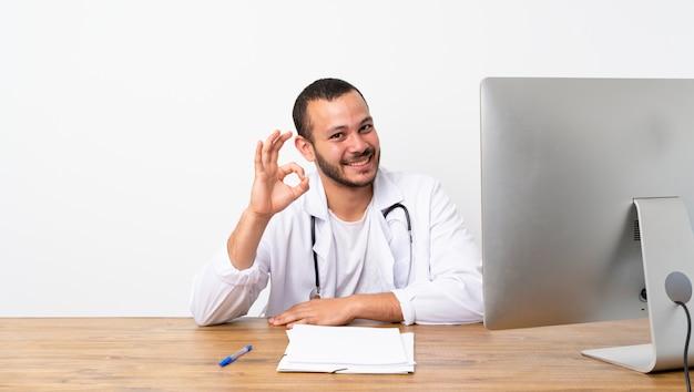 Uomo colombiano del dottore che mostra segno giusto con le dita