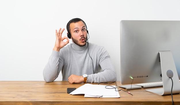 Uomo colombiano di telemarketer sorpreso e che mostra segno giusto