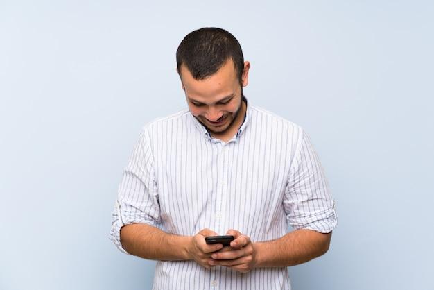 Uomo colombiano sopra isolato muro blu inviando un messaggio con il cellulare