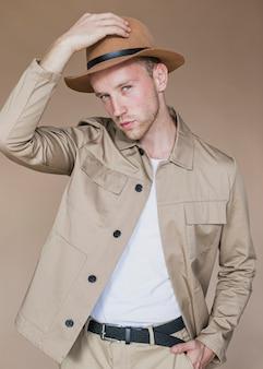 Uomo comprensivo con cappello su uno sfondo marrone