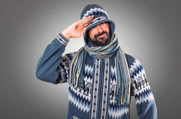 Uomo con abiti invernali saluto su sfondo grigio