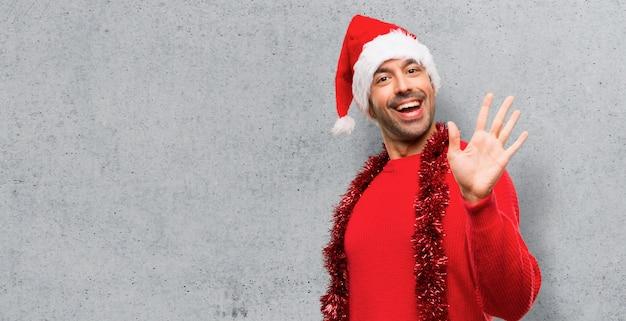 Uomo con abiti rossi che celebra le feste di natale salutando con la mano