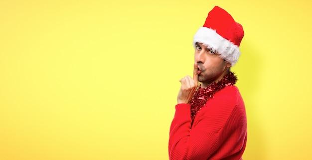 Uomo con abiti rossi che celebrano le vacanze di natale mostrando un segno di chiusura della bocca