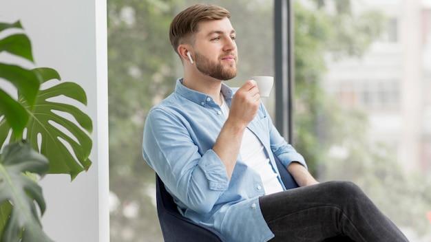 Uomo con airpods che beve caffè