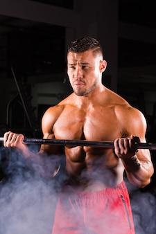 Uomo con allenamento con i pesi nel club sportivo attrezzature da palestra