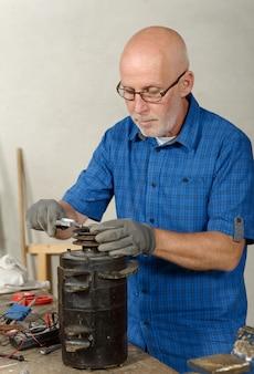 Uomo con antico generatore per l'auto