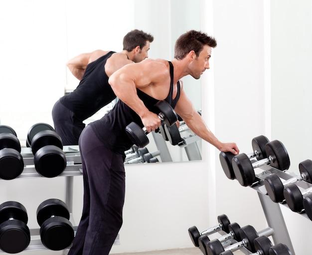 Uomo con attrezzature allenamento con i pesi in palestra sportiva