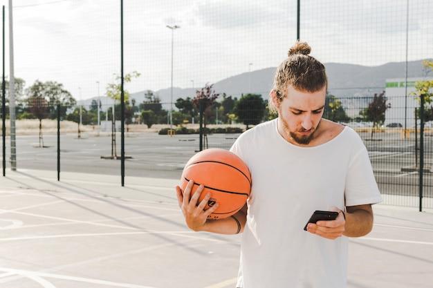 Uomo con backetball guardando il telefono cellulare in tribunale