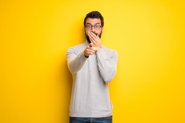 Uomo con barba e collo alto che puntava il dito contro qualcuno e rideva