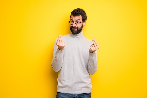 Uomo con barba e collo alto facendo soldi gesto