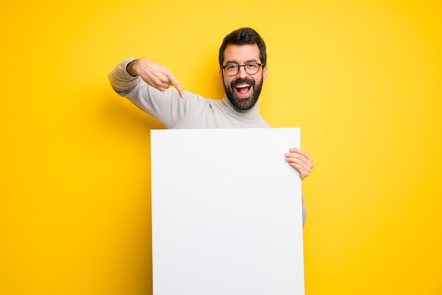 Uomo con barba e collo alto in possesso di un cartello bianco vuoto