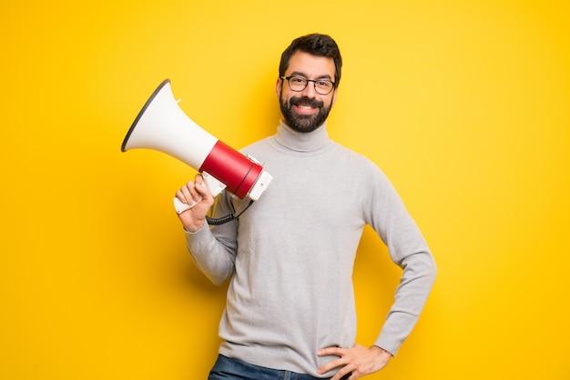 Uomo con barba e collo alto in possesso di un megafono