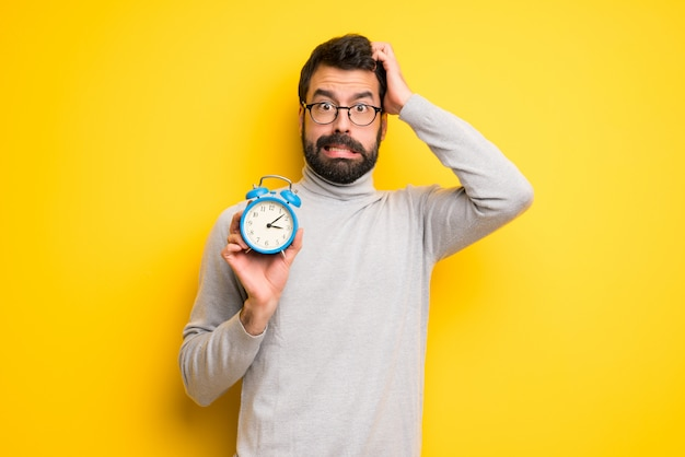 Uomo con barba e collo alto inquieto perché è tardi e tiene sveglia vintage
