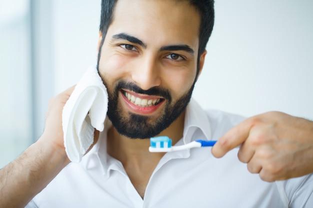 Uomo con bel sorriso, denti bianchi sani con spazzolino.