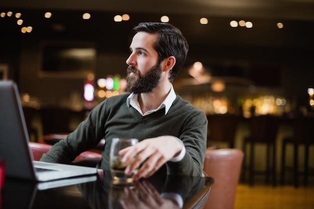 Uomo con bicchiere di bevanda e computer portatile sul tavolo