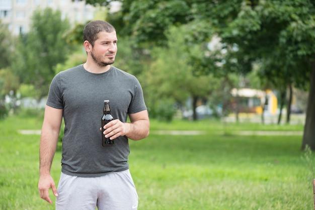 Uomo con birra guardando lontano nel parco