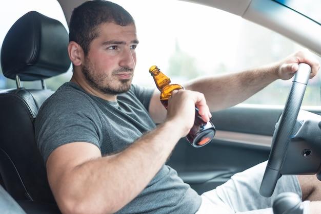 Uomo con birra guida auto