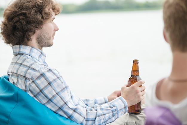 Uomo con birra rilassante vicino fiume e amico