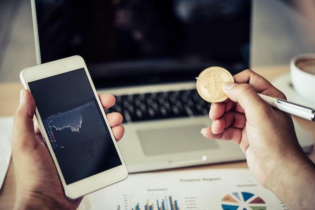 Uomo con bitcoin e grafico defocused nel telefono cellulare