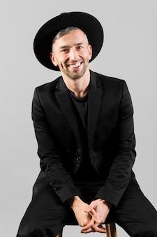 Uomo con black hat che sorride e che si siede sulla sedia