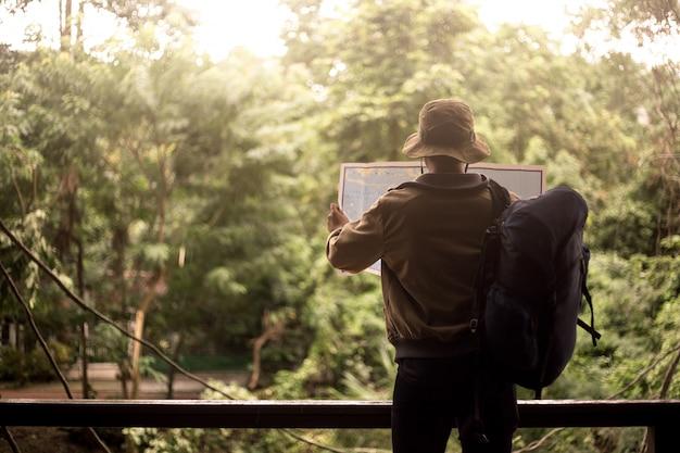 Uomo con borsa, cappuccio e in possesso di una mappa