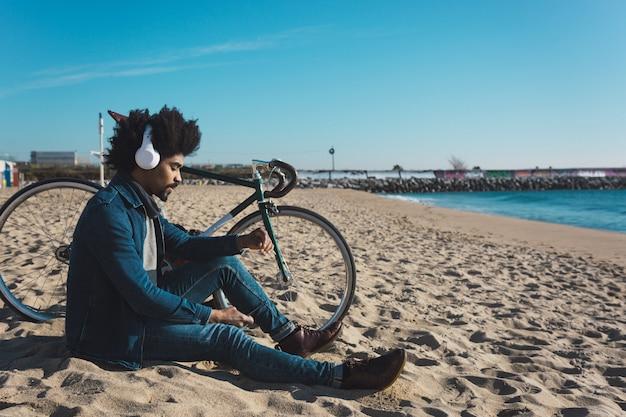 Uomo con capelli afro in sella a una bicicletta in stile vintage