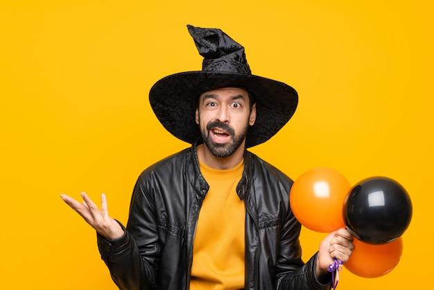 Uomo con cappello da strega che tiene mongolfiere nere e arancioni per la festa di halloween facendo dubbi gesto