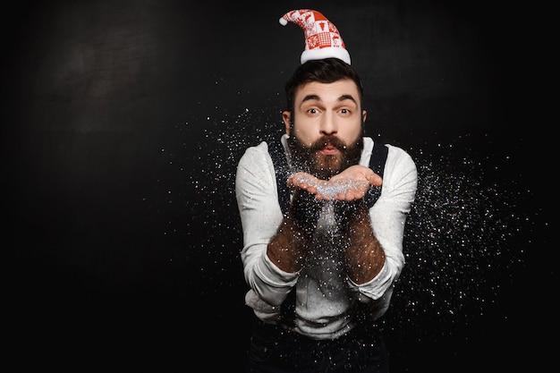 Uomo con cappello di babbo natale che soffia glitter argento sul nero.