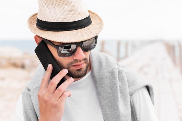 Uomo con cappello e occhiali da sole parlando su smartphone