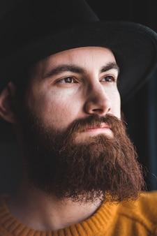 Uomo con cappello nero e maglia arancione