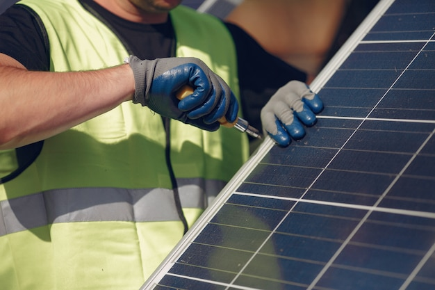 Uomo con casco bianco vicino a un pannello solare
